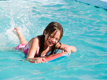 Laughing Girl in Pool. Young girl splashing on a boogie board in  a clear blue swimming pool Royalty Free Stock Photography