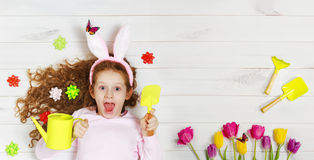 Laughing girl in rabbit ears lying on the wooden floor. Royalty Free Stock Images