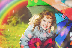 Laughing girl in the rain with a rainbow and with color bokeh. Happy and healthy childhood concept Stock Photography