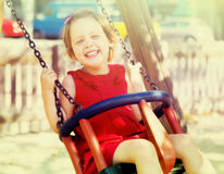 Laughing girl in red  on chain swing Stock Photos