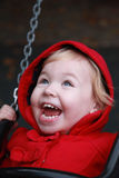 Laughing girl in red clothes on chain swing Stock Photography