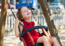 Laughing girl in red dres on  swing Royalty Free Stock Image