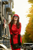Laughing girl in red dress on the sun street Stock Photo