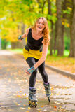 Laughing girl roller-skating in the autumn park Royalty Free Stock Images