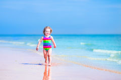 Laughing girl running on a beach Stock Image