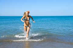 Girl runs out of the sea Royalty Free Stock Image