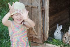 Laughing girl showing hands in front of farm hutch with domestic rabbits. Outdoors Royalty Free Stock Image