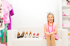 Laughing girl sits on sofa choosing shoes Royalty Free Stock Photography