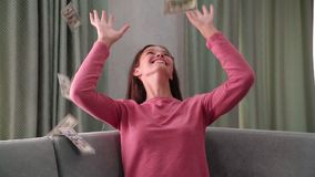 Laughing girl sits on sofa under banknotes rain slow motion. Laughing happy girl teenager sits on grey sofa under money banknotes rain falling down from ceiling stock video footage