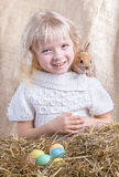 Laughing girl with sitting on the back of the Easter bunny Royalty Free Stock Photos