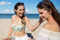 Laughing girl sitting on beach with friend touching her cheek Royalty Free Stock Photography