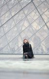 Laughing girl sitting near the Louvre pyramid Stock Photos