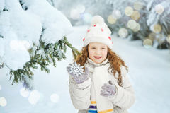 Laughing girl with snowflakes in his hand, in winter park. Happy Christmas day. Holiday and childhood concept royalty free stock image