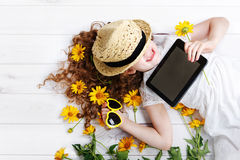 Laughing girl in a straw hat resting on the tablet in her hands. stock images