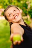 Laughing girl stretches an apple. The young beautiful girl holds an apple in a hand and laughs against a summer garden Royalty Free Stock Photography