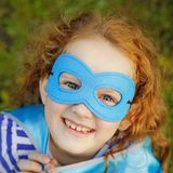 Laughing girl with superhero mask. Laughing child with superhero mask showing white teeth. Happy childhood concept royalty free stock image