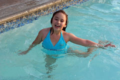 Laughing girl in swimming pool. A laughing 6-year-old girl plays in a swimming pool. She has big brown eyes and brown hair and is of Asian and Caucasian Stock Image