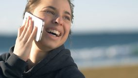 Laughing Girl talking on phone smiling looking happy outdoors. Outdoors girl talking on mobile cell phone close up smiling and happy shot in slowmotion stock video