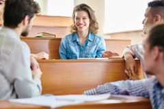 Laughing girl talking to groupmates in lecture room. Cheerful excited pretty student girl laughing while talking to male groupmates and sitting at wooden desk in Stock Photos