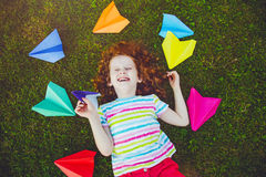 Laughing girl throwing paper airplane in green grass at summer p Royalty Free Stock Photography
