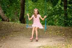 Laughing girl on a tree swings Stock Photo