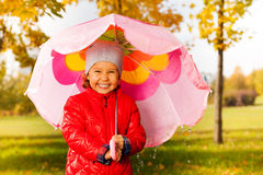 Laughing girl with umbrella standing under rain Royalty Free Stock Image