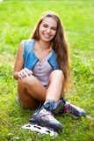 Girl wearing roller skates sitting on grass Stock Image