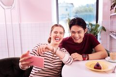 Laughing girlfriend making memorable selfie with her man. Lovely selfie. Laughing beautiful girlfriend feeling amazing while making memorable selfie with her man royalty free stock images