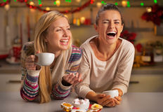 Laughing girlfriends having christmas snacks Stock Image