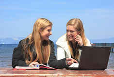 Laughing Girls. Two teen aged girl students sitting at a park bench laughing and studying with a book and computer Royalty Free Stock Photography
