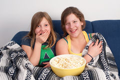 Laughing girls. Two girls on sofa eating popcorn and watching tv Royalty Free Stock Photos