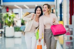 Laughing girls carrying bags with purchases in shopping mall.  stock photos