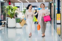 Laughing girls carrying bags with purchases in shopping mall.  stock images
