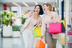 Laughing girls carrying bags with purchases in shopping mall.  royalty free stock images
