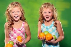 Laughing girls holding some fruit. Little laughing girls holding apples and oranges Stock Photos