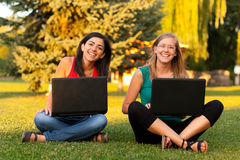 Laughing girls outdoors with laptop. Two happy girl outdoors with their laptops sitting on grass Stock Photos