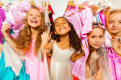Laughing girls standing among colorful dresses. Laughing girls during shopping standing among colorful bright dresses and children clothes on hangers in the stock photos