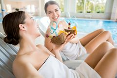 Happy talk. Laughing girls with tropical cocktails enjoying rest at luxurious spa resort Royalty Free Stock Image