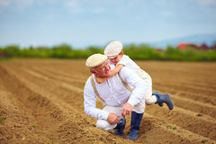 Laughing grandfather and grandson having fun on spring field, countryside Stock Photography