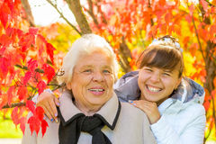 Laughing grandmother and granddaughter. In the park with beautiful red leaves Stock Photography