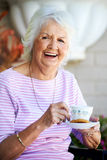 Laughing Grandmother. Grandmother laughing and positive having some tea Stock Image