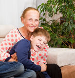Laughing grandson hugs with grandmother. Laughing happy grandson hugs with grandmother Stock Photos
