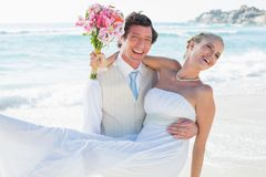 Laughing groom carrying his pretty blonde wife smiling at camera Stock Image
