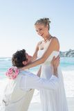Laughing groom picking up his pretty blonde wife Stock Images