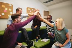 Laughing group of designers high fiving during an office meeting. Laughing group of diverse designers sitting on a sofa in a modern office high fiving together stock photo