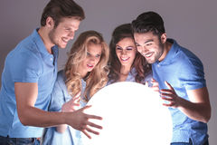 Laughing group of friends reading in a crystal ball Stock Image