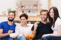 Laughing group of friends watching television Stock Image