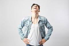Laughing guy dark-haired guy dressed in a white t-shirt and a denim jacket stands on the white background in the studio stock photo