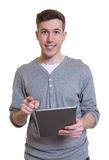 Laughing guy in a grey shirt working with tablet computer Stock Images