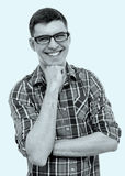 Laughing guy with hand on chin. Blue toned black and white portrait of young man wearing glasses and checkered shirt standing with fist under his chin and Royalty Free Stock Photos